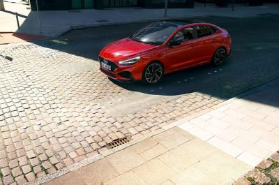 A new Hyundai i30 Fastback N Line parked on a cobblestone street