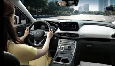Interior view of the new Hyundai Santa Fe 7 seat SUV with a woman driving through a city.